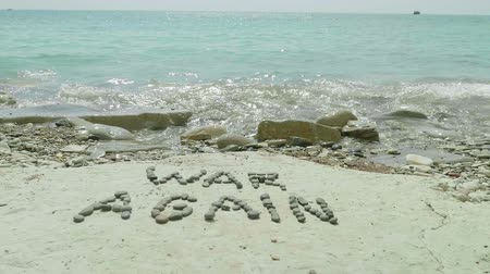 sem problemas : Slow motion view of writing war again made with stones on sea shore