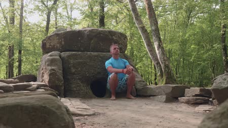 boulders : Caucasian man sits thoughtfully next to the ancient dolmen