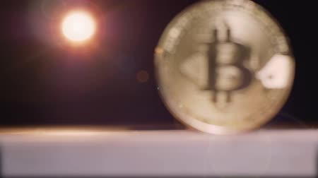 telephoto lens : Coin bitcoin is removed and becomes in focus in backlight and on black background Stock Footage