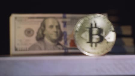 Франклин : Real gold coin Bitcoin against the background of a pack of dollars us. Focus change Стоковые видеозаписи