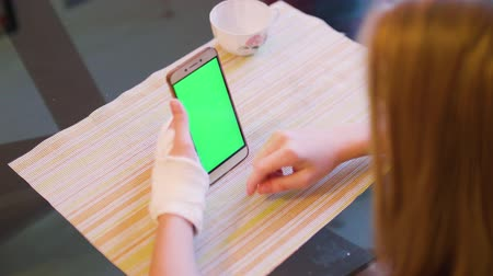 keying : Young caucasian blonde sit at table with broken left hand and look at green screen of smartphone