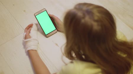 vertically : Young caucasian blonde with broken left hand look at green screen of the smartphone. Close-up view Stock Footage