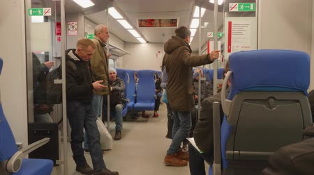heures : MOSCOW - CIRCA NOVEMBER 2017: People standing and sitting in carriage of train of Moscow central circle Vidéos Libres De Droits