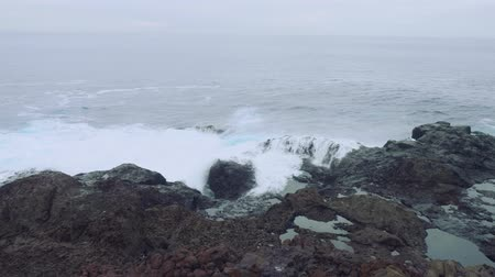 stony : Waves of stormy sea are breaking on rocky shore. Stock Footage