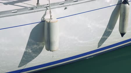 fender : Two kinds of fender haning down from yacht board