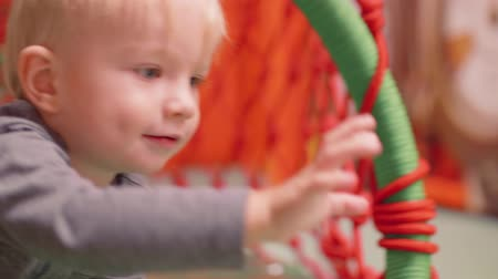 first born : Blond toddler creeps to catch ball Stock Footage