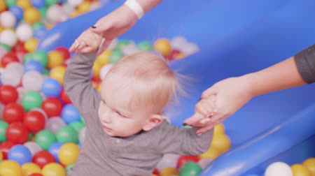 first born : Mom pulls out little son from plenty of balls in dry pool Stock Footage