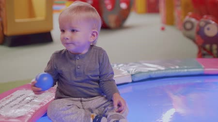 first born : Blond toddler sits on artificial pool with dry surface Stock Footage