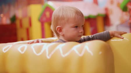 first born : Blond toddler on chair of big yellow car