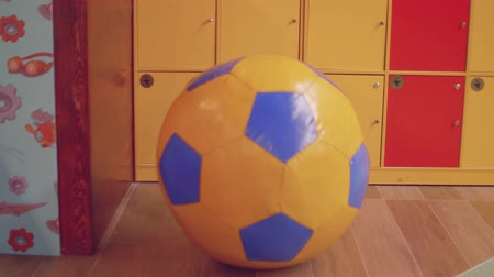 View of huge football ball pushed by blond toddler