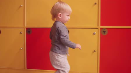Blond todd;er closes doors of lockers Stock Footage