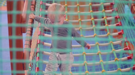 first born : Blond toddler plays in net