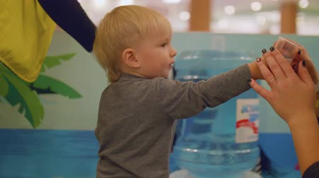 first born : Mom gives plastic glass with water to her son and he drinks