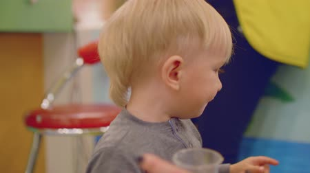 first born : Blond toddler looks at camera and drinks water