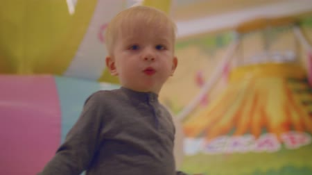 first born : Blond toddler pulls toy car chewing orange Stock Footage