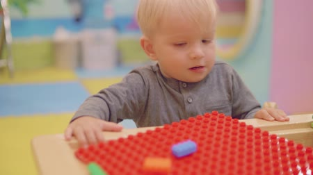 first born : Blond toddler starts playing with construction kit