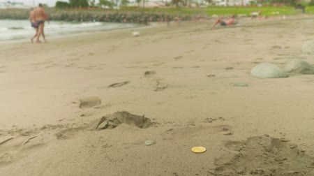 cultura juvenil : Zoom in of bitcoin lying on sand with blurred people resting on beach on background Stock Footage