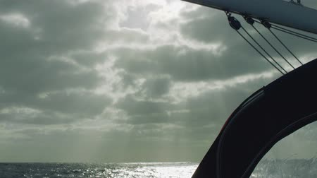 greatness : Cold sun rays creeping trough clouds and lighting up ocean surface Stock Footage