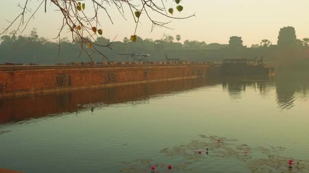 к юго западу : View of stone bridge leading to Angkor Wat temple early in morning. Its closed for restoration period