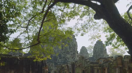Ангкор : View of Angkor Wat temple trough green leaves of trees