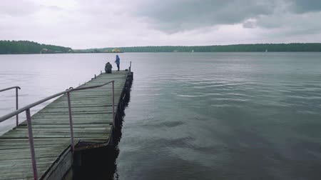 dull : Two men fishing on old wooden pier Stock Footage
