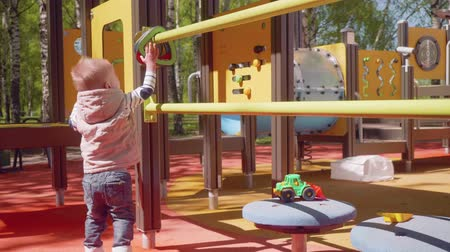 sassy : Little blond boy plays on palyground in park.