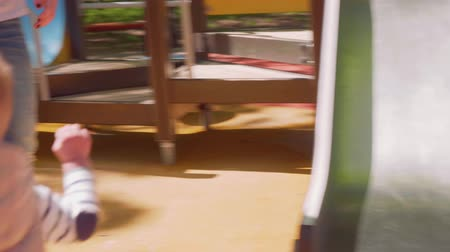 adore : Little blond toddler slides down from playground slide