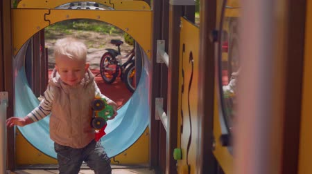 angyali : Little blond toddler approaches camera playing on playground