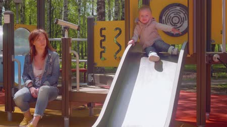 внимательный : Blond toddler slides down from playground slide Стоковые видеозаписи