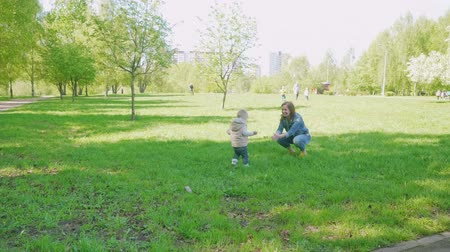 kabarcıklı : Blond toddler runs to his mom sitting on green grass