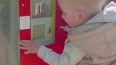 Little blond son pushes buttons of drink dispenser in park