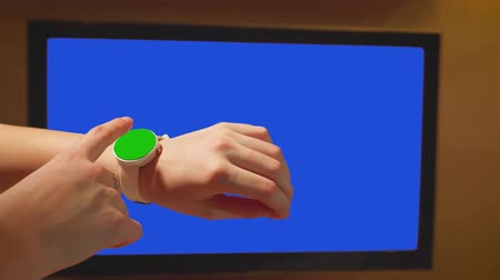 heart rate : Girl touches green screen watches. Blue screen TV set on background