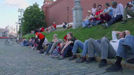 fan zone : Tourists sit on green grass near Kremlin wall on red square