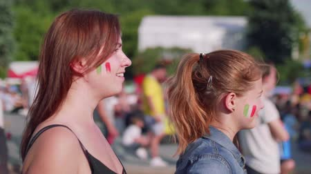 french team : Girls happily hug each other during watching football match in fan zone