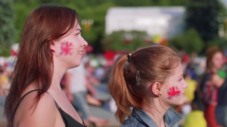 fan zone : Girls with Britain flag on cheeks watch football game in fan zone Stock Footage