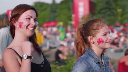 végső : Girls with Britain flag on cheeks watch football match in fan zone