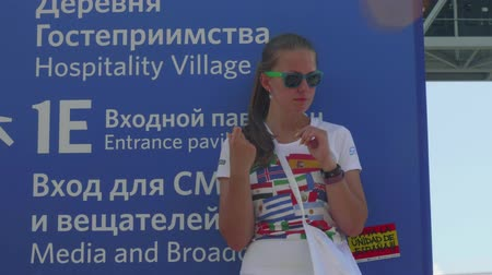 fan zone : MOSCOW - CIRCA JULY, 2018: Valunteer girl on stilts entertains football fans before football match in Luzhnkik stadium Stock Footage