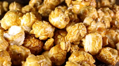 caramelo : Sweet caramel popcorn on wooden background. Macro shot. Vídeos