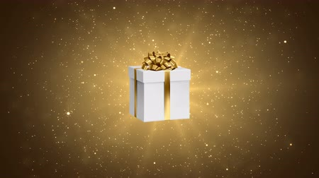 hediye kutusu : White gift with gold bow on the festive gold background. Holiday abstract loop animation. Stok Video