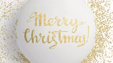 csillogás : Hanging elegant Christmas evening ball with shining gold snowflake and congratulatory inscription on the holiday white background. 4K motion graphic.