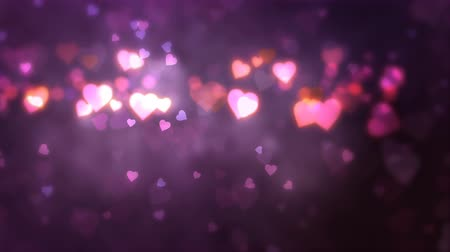 Glowing hearts appear on the shining purple background. Valentines Day holiday abstract loop animation.