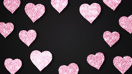 Pink shining hearts sparkle on the black background with place for text. Valentines Day holiday abstract loop animation.