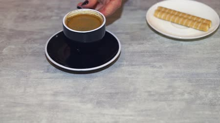 csészealj : A female hand puts a cup of coffee on a saucer and serves sweet biscuits