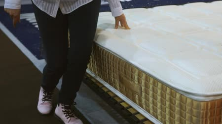 colchão : A woman in a white shirt examines the mattress, she squats and and sits down at the mattress Stock Footage