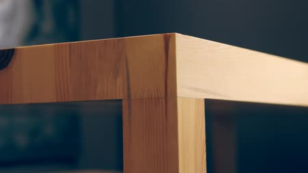столовая : Trendy wooden table angle made without a single nail in a room with dark purple walls