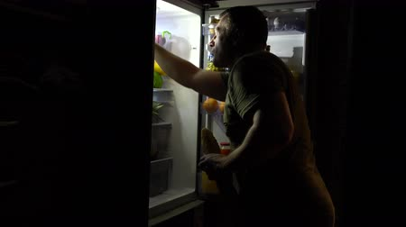 жадный : Middle aged man opening refrigerator for snack Стоковые видеозаписи