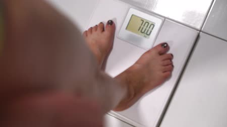 libras : Woman stepping onto a bathroom scale