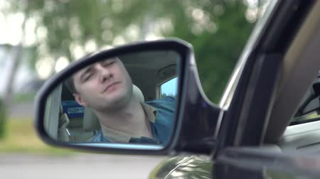 stationary : Young man driving a car checking behind him