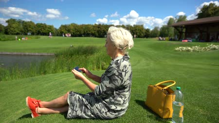 engrossed : Mature woman sitting on green grass