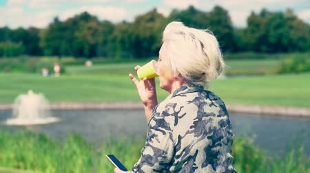 engrossed : Woman drinking beverage from small yellow cup Stock Footage